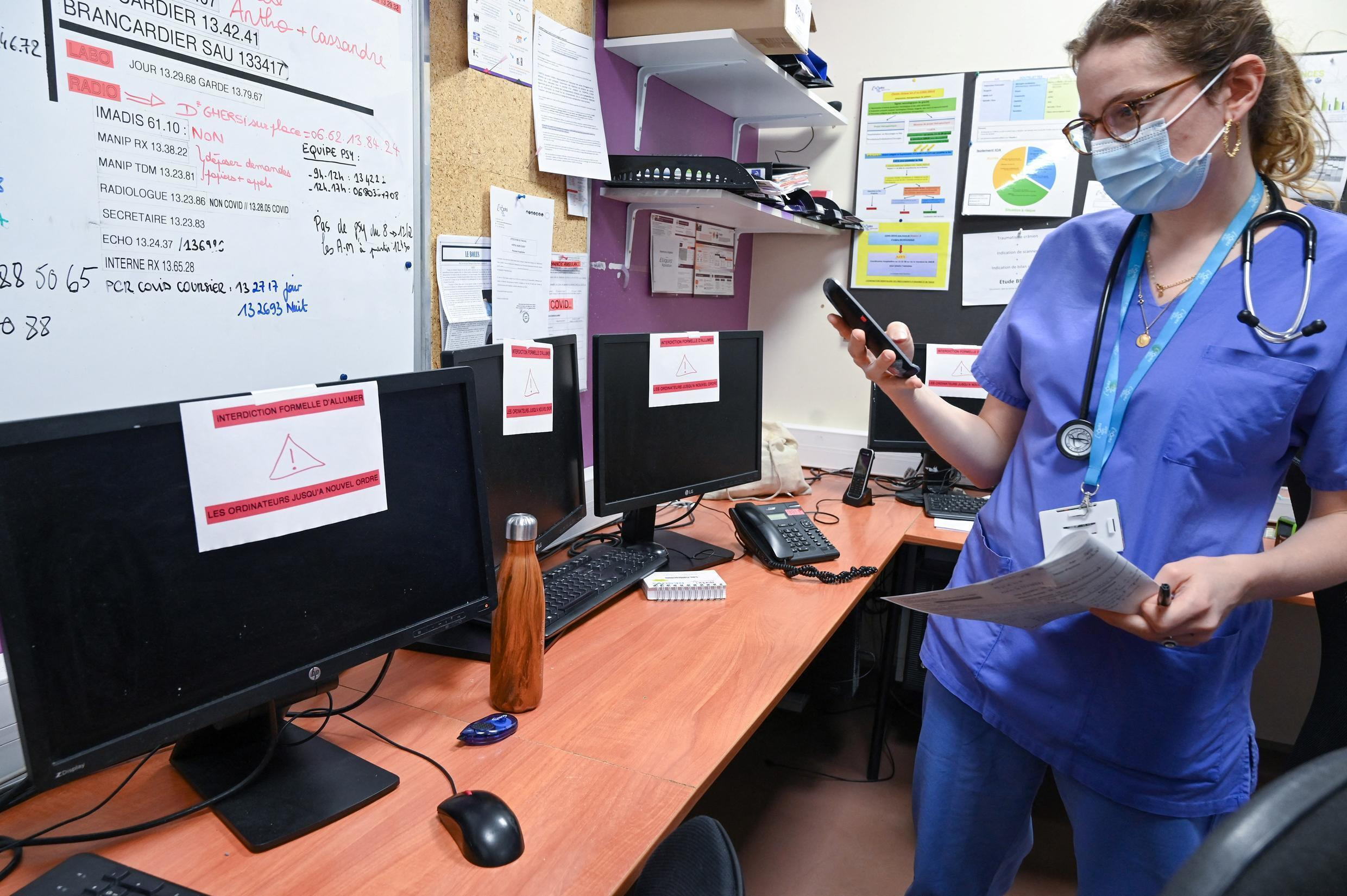 A nurse stands in front of out-of-service computers following a cyber attack on Villefranche-sur-Saône's hospital complex in eastern France on February 16, 2021.