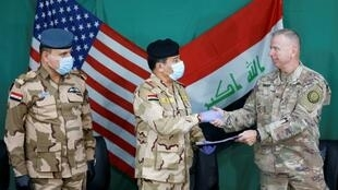 FILE PHOTO: U.S. Brigadier General Vincent Barker (R) shakes hands with Iraqi General Mohammed Fadel (C), wearing face mask and gloves, following the outbreak of coronvavirus disease (COVID-19), during the hand over of Qayyarah Airfield West from US-led coalition forces to Iraqi Security Forces, in the south of Mosul, Iraq March 26, 2020.