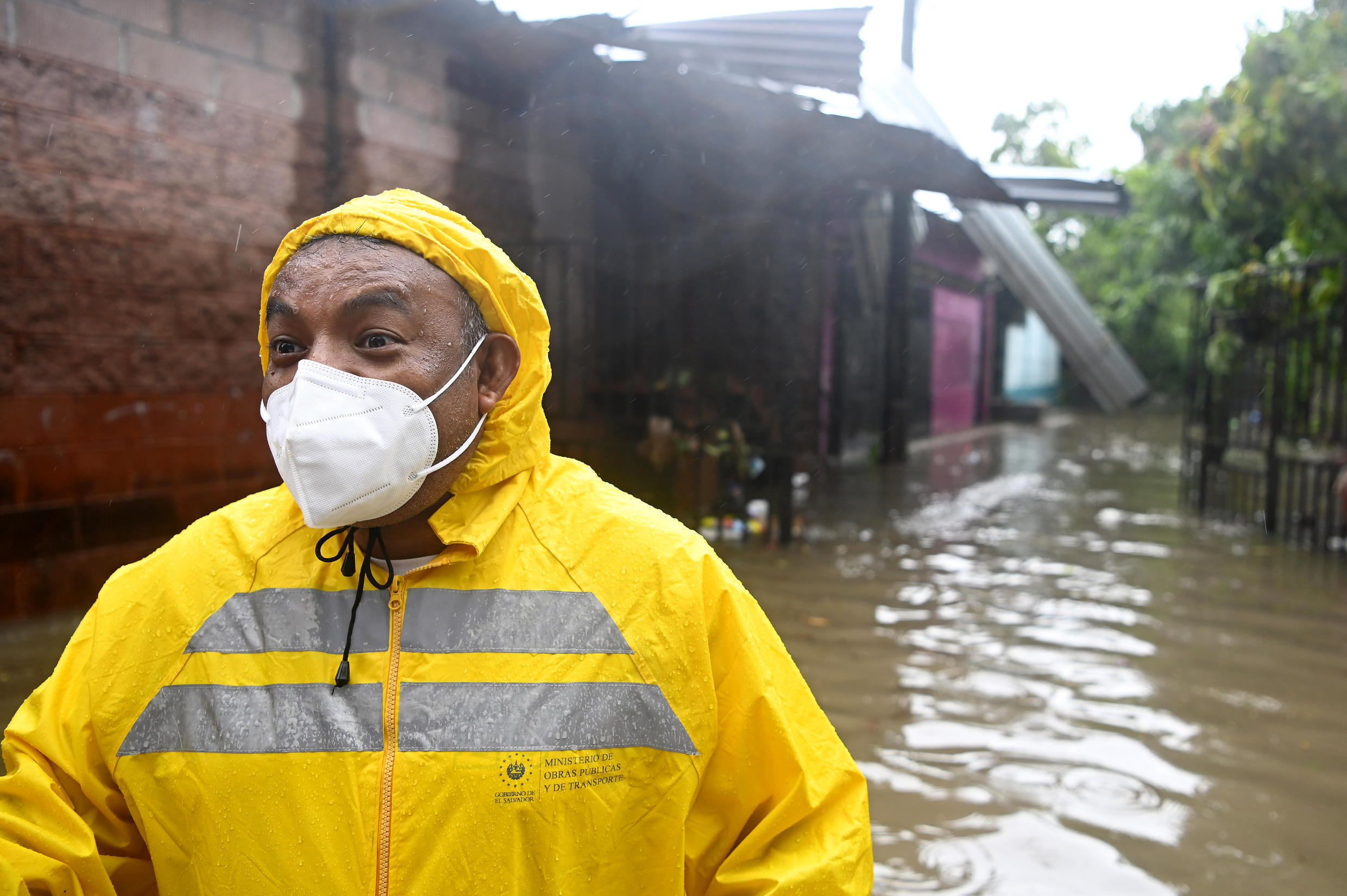 An employee of the Public Works Ministry is seen in the flooded Santa Lucia colony in Ilopango, El Salvador, during Tropical Storm Amanda