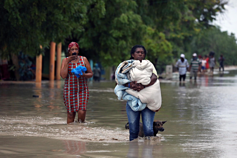 Des habitants d'Azua, en République dominicaine, tentent de sauver leurs effets personnels des inondations après le passage de la tempête Laura, le 23 août 2020.