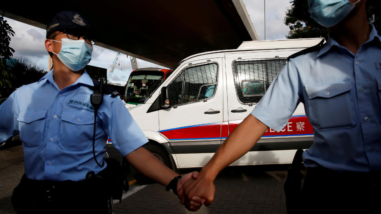 Des policiers protège un fourgon transportant Tong Ying-kit, la première personne accusée en vertu de la nouvelle loi sur la sécurité nationale, alors qu'il quitte le tribunal de West Kowloon, à Hong Kong, en Chine, le 6 juillet 2020.