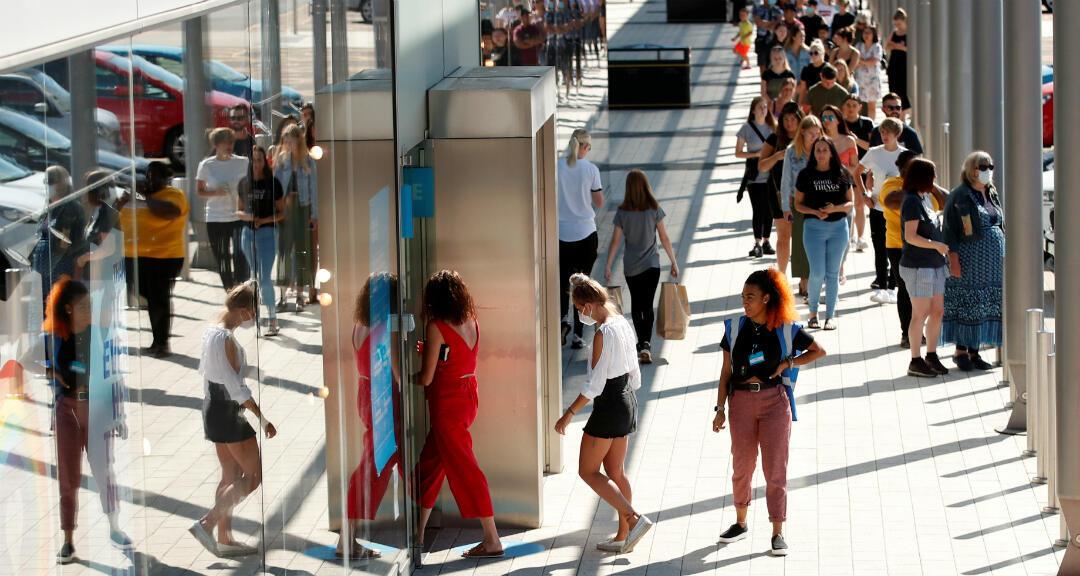 Gente hace fila para ingresar a una tienda de la cadena Primark el día en que el comercio abre nuevamente tras el confinamiento por la pandemia de coronavirus en Milton Keynes, Reino Unido, el 15 de junio de 2020.
