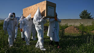 Relatives wear PPE to carry the coffin of a COVID-19 victim in Kashmir