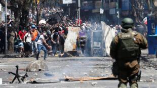 Los manifestantes se reúnen detrás de una barricada mientras chocan con las fuerzas de seguridad durante una protesta contra el modelo económico estatal de Chile en Valparaíso, Chile, el 21 de octubre de 2019.