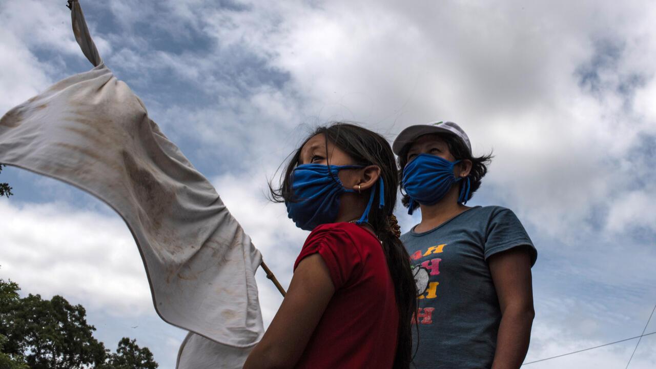 Una mujer y su hija piden ayuda con una bandera blanca improvisada durante la cuarentena obligatoria decretada por el gobierno de El Salvador contra la propagación del nuevo coronavirus, San Luis Talpa, El Salvador, el 29 de mayo de 2020.