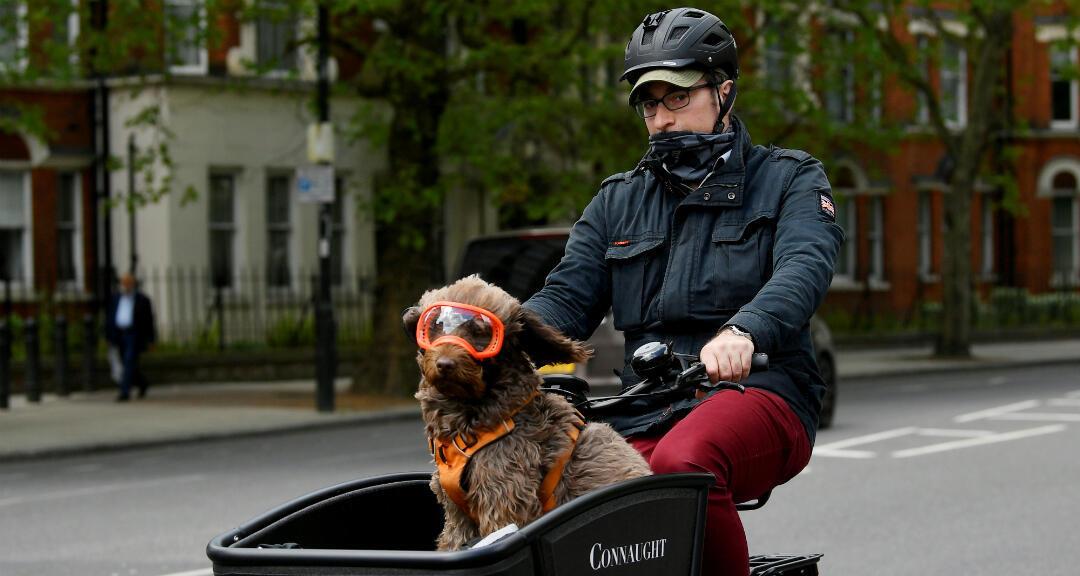 Un hombre lleva a su perro en una bicicleta en el centro de Londres, Reino Unido, el 4 de mayo de 2020.