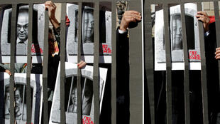 Albert Gea, REUTERS | Pictures of jailed Catalan politicians are placed behind prison bars made of paper during a protest in Barcelona on February 12, 2019.