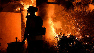 Los bomberos combaten un incendio forestal impulsado por el viento en la madrugada del viernes en Porter Ranch, California, EE. UU., el 11 de octubre de 2019.