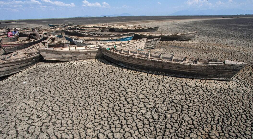 Archivo-Hombres sentados en botes estacionarios sin motor que yacen inactivos en el puerto seco de la isla Chisi del lago Chilwa en el interior del distrito de Zomba, al este de Malawi, en medio del aumento de la temperatura global, del nivel del mar y la intensificación de los eventos del clima extremos. Imagen tomada el 18 de octubre de 2018.