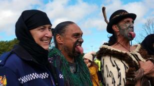 Una oficial de policía con un velo en la cabeza posa este 22 de marzo de 2019 con dos hombres maoríes vestidos con un atuendo tradicional durante una conmemoración para las víctimas de las masacres de mezquitas en Christchurch.