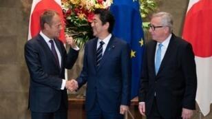 رئيس الوزراء الياباني شينزو آبي (وسط) مصافحا رئيس المجلس الأوروبي دونالد توسك بحضور رئيس المفوضية الأوروبية جان-كلود يونكر في طوكيو في 17 تموز/يوليو 2018