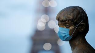 Une statue du Trocadéro portant un masque de protection à Paris devant la Tour Eiffel.