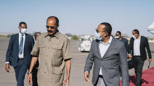 Ethiopian PM Abiy Ahmed (R) and Eritrea's President Isaias Afwerki speaking upon the arrival of the latter for a bilateral meeting at Asmara International Airport in Asmara on March 25, 2021.