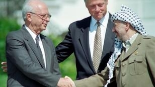 US president Bill Clinton stands between PLO leader Yasser Arafat and Israeli Prime Minister Yitzahk Rabin as they shake hands on September 13, 1993 at the White House after signing the Oslo Accords