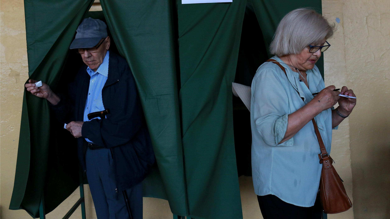 Dos ciudadanos chilenos salen del cuarto oscuro durante las elecciones de segunda vuelta presidencial, el 17 de diciembre, las cuales marcaron el cierre del calendario electoral de América Latina de 2017.