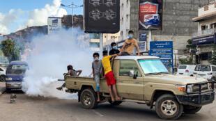 Des garçons portant des masques de protection à l'arrière d'une camionnette qui mène une opération de fumigation pour éviter la propagation de maladies à Aden (sud du Yémen), le 5 mai 2020, en pleine pandémie du coronavirus