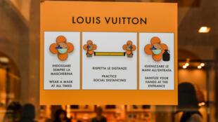 Un cartel informa de la distancia social a mantener en una tienda de la firma de lujo Louis Vuitton en la ciudad italiana de Milán el 18 de mayo de 2020