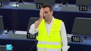 النائب فلوريان فيليبو يقف أمام البرلمان الأوروبي مرتديا سترة صفراء وواضعا يده على عينه اليمنى في إشارة إلى الإصابات التي وقعت في المظاهرات