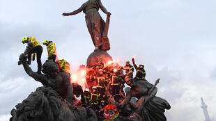 Firefighters brandish flares as they climb on the Statue of Republic Triumph at Nation square during a demonstration to protest against French government's plan to overhaul the country's retirement system in Paris, on January 28, 2020.