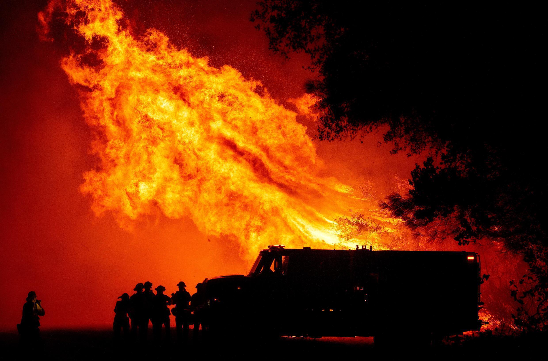 Los bomberos del condado de Butte observan cómo las llamas se elevan sobre su camión, en el incendio Bear en Oroville, California, uno de los varios incendios forestales que azotan la costa del Pacífico de EE. UU.