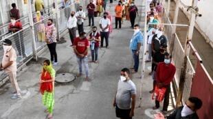 مصلون هندوس ينتظرون في طوابير للصلاة في معبد جاندوالان في نيودلهي في 8 حزيران/يونيو 2020.