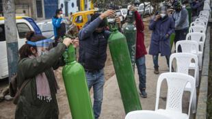 Familiares de los pacientes con covid-19 hacen cola para recargar los cilindros de oxígeno en Villa María del Triunfo, en las afueras de Lima, el 29 de julio de 2020