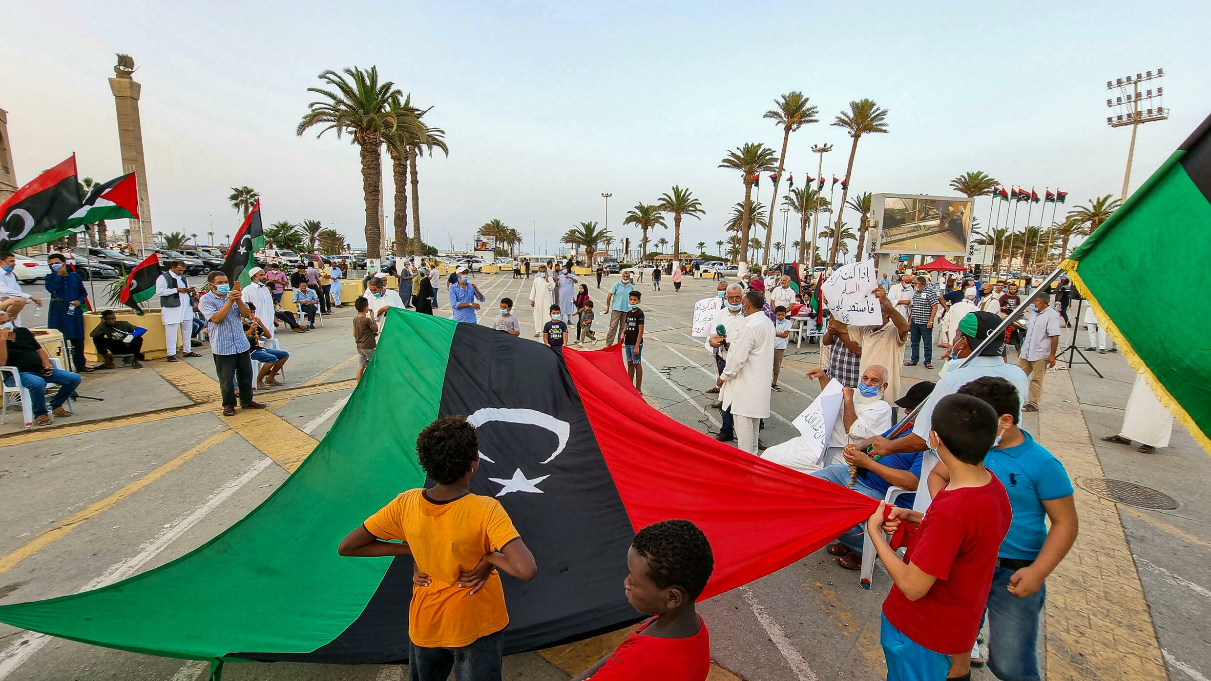 People gather with Libyan national flags at the Martyrs' Square in the centre of Tripoli on August 20, to mark the 10th anniversary of the city's capture from the forces of former leader Moamer Kadhafi