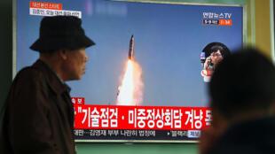 Un homme passe devant un écran de télévision sur lequel s'affiche l'image d'un missile nord-coréen, le 5 avril 2017, dans une gare de Séoul.