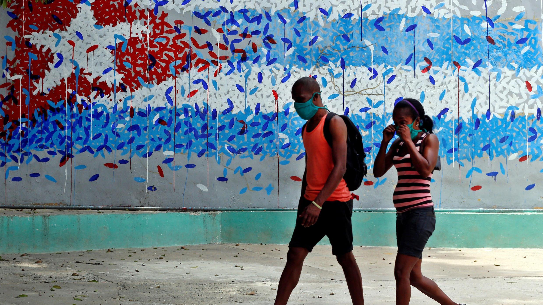 Una pareja con tapabocas fue registrada este 7 de mayo al caminar junto a una pintura artística de la bandera cubana, en La Habana (Cuba)