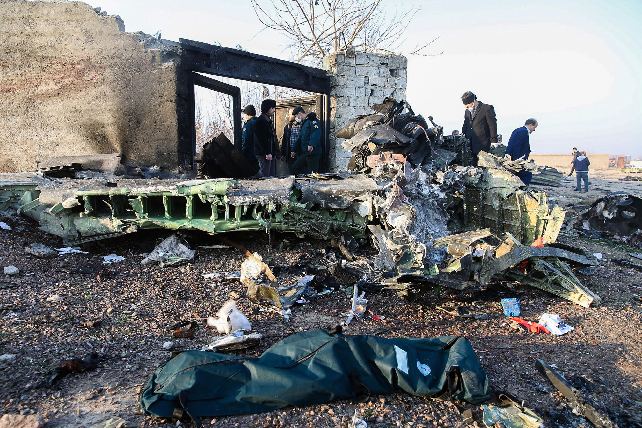 People stand near the wreckage after a Ukrainian plane carrying 176 passengers crashed near Imam Khomeini airport in Tehran on January 8, 2020.