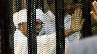 الرئيس السوداني السابق عمر البشير يلوح من وراء القضبان أثناء محاكمته في الخرطوم، 19 أغسطس/آب 2019.