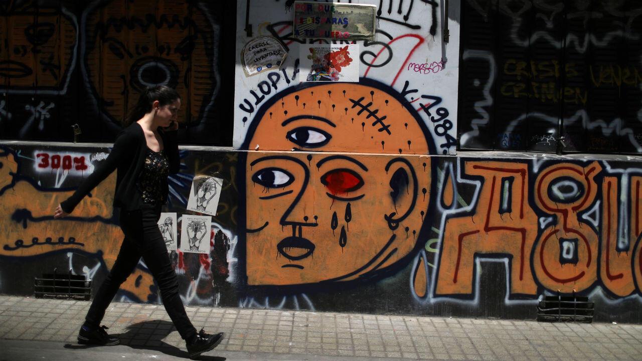 Un manifestant passe devant une fresque de soutien aux éborgnés de la mobilisation au Chili.