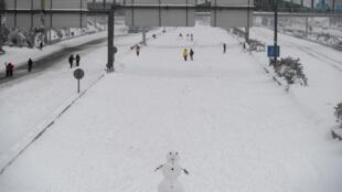 Un bonhomme de neige est construit le long de la rocade M30 au milieu de fortes chutes de neige à Madrid, le 9 janvier 2021.