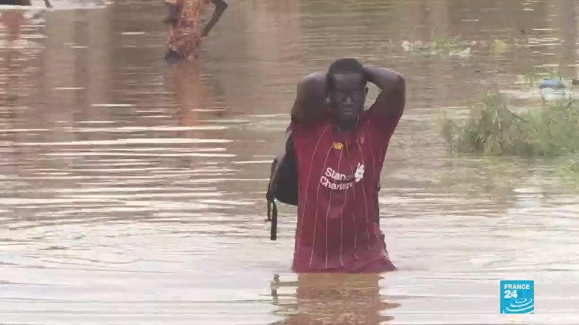 A man wades through floodwaters in Keur Massar, a suburb of Dakar, Senegal.