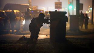 Un policier se met à couvert, lundi 18 août, à Ferguson.