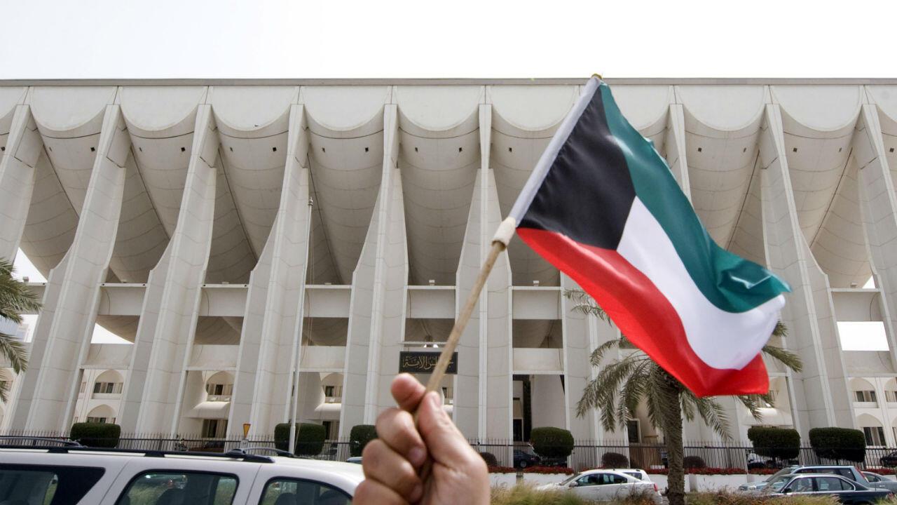 شخص يحمل علم الكويت أمام مبنى مجلس الأمة الكويتي.