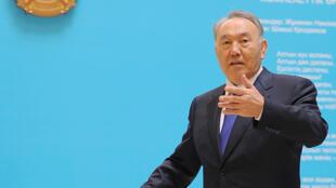 Noursoultan Nazarbaïev glissant son bulletin dans l'urne, dimanche 26 avril, à Astana.