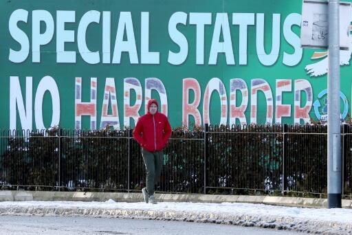 Un transeúnte pasa el 8 de diciembre de 2017 por delante de un cartel del partido republicano Sinn Féin en el oeste de Belfast pidiendo un estatus especial para Irlanda del Norte con respecto al Brexit