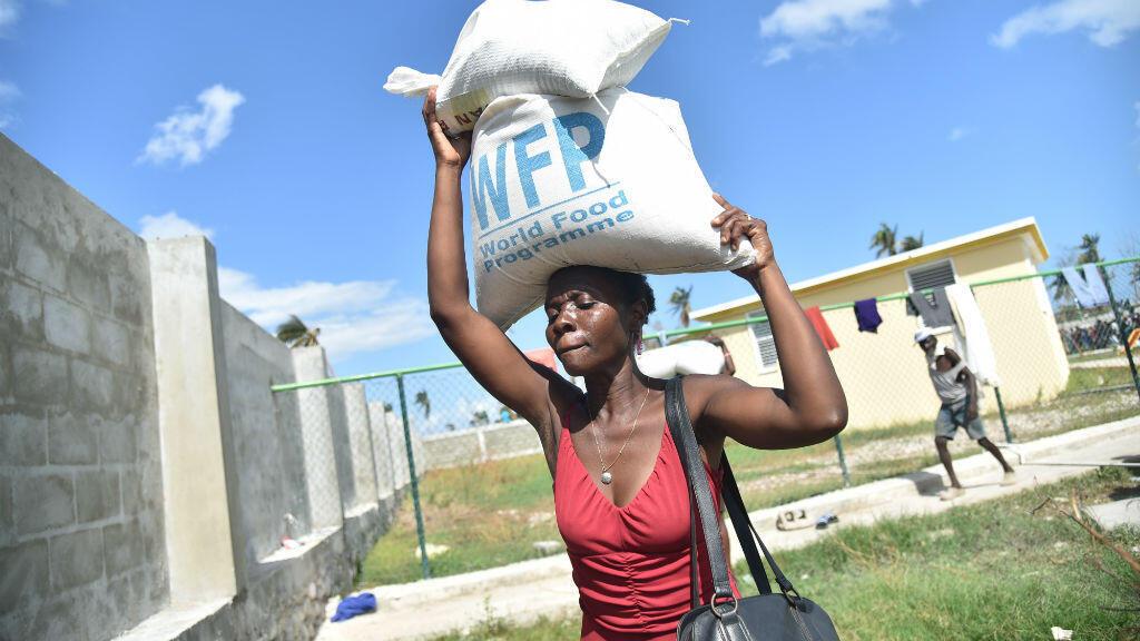 Une femme transporte un sac de nourriture à Les Cayes, en Haïti, le 13 octobre 2016.