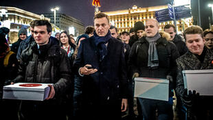 Supporters of Russian opposition leader Alexey Navalny (C) carry boxes with signatures to nominate him as opposition candidate for the forthcoming presidential election in Moscow on December 24, 2017. Alexei Navalny, seen as the only Russian opposition leader who stands a fighting chance of challenging strongman Vladimir Putin, seeks to get his name on the ballot for a March vote, with supporters gathering across Russia to endorse the move.