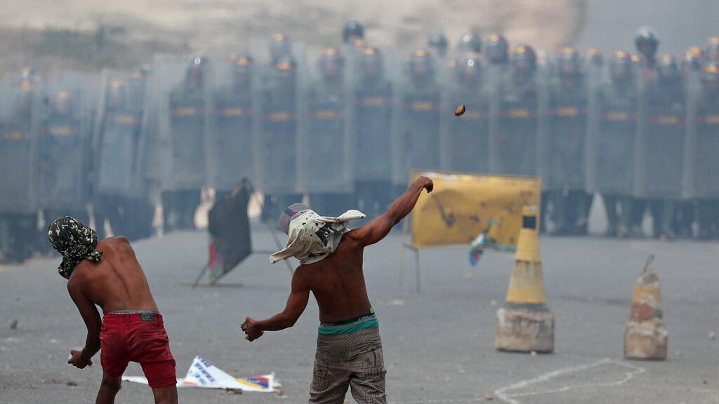 Manifestantes arrojan piedras a la Guardia Nacional de Venezuela en Pacaraima, Brasil, el 24 de febrero de 2019.