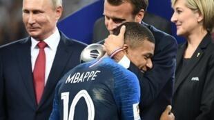 كيليان مبابي (19 عاما) معانقا الرئيس الفرنسي بعد مباراة النهائي، روسيا 15 تموز/يوليو 2018.