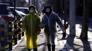 Women wear face masks and plastic raincoats as a protection from coronavirus in Shanghai, China February 17, 2020. REUTERS OK