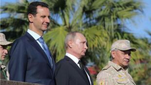 El presidente ruso Vladimir Putin (C), el ministro de Defensa Sergei Shoigu (R) y el presidente sirio Bashar al-Assad visitan la base aérea de Hmeymim en la provincia de Latakia, Siria, el 11 de diciembre de 2017.