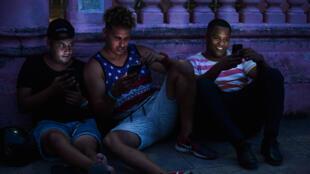 Jóvenes cubanos se conectan a Internet desde su teléfono móvil en La Habana, el 6 de junio de 2019. Los cubanos no ocultan su frustración seis meses después de la llegada de Internet móvil a la isla ya que la conectividad es cara, lenta y controlada por el Gobierno.