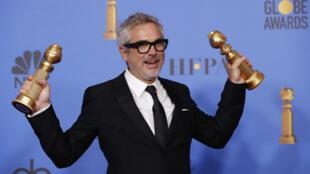 """Alfonso Cuarón posa detrás del escenario con su estatuilla a mejor director y mejor película extranjera con """"Roma"""", en la 76 edición de los Globos de Oro en Beverly Hills, California, EE. UU., el 6 de enero de 2019."""