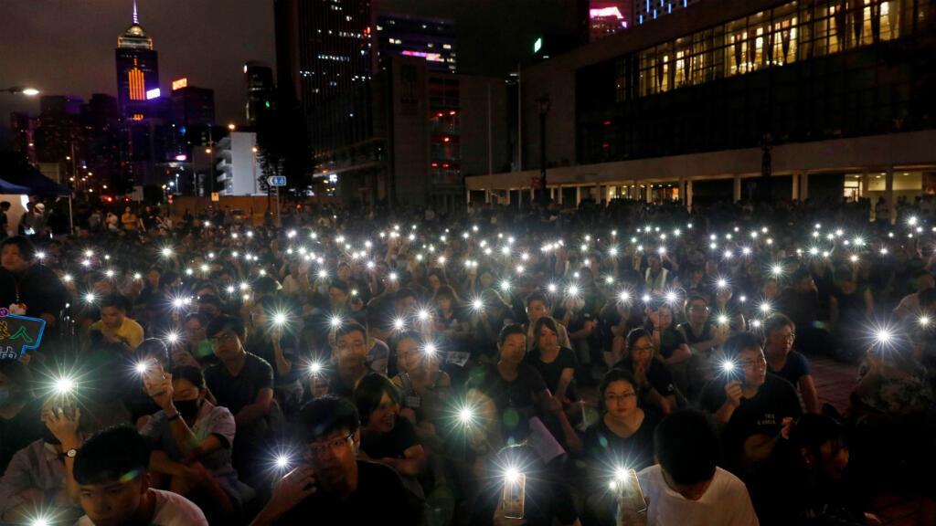 Miembros del sector médico de Hong Kong encienden sus teléfonos móviles durante una manifestación contra el Gobierno hongkonés, al que exigen más garantías de libertad y democracia. Hong Kong, China, el 2 de agosto de 2019.