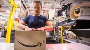 Une employée d'Amazon, en train d'empaqueter un article. Sur la boîte, le logo de l'entreprise.