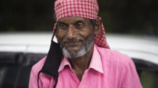 En Nueva Delhi, un conductor de 'rickshaw' (bicitaxi) espera a un cliente  con su mascarilla suspendida a una oreja, el 7 de julio de 2020
