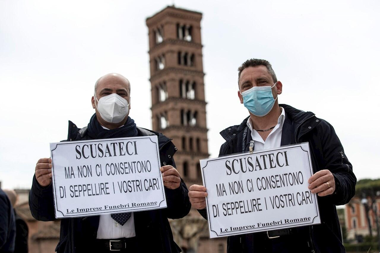 Funeral workers protest at the Bocca della Verita with banners reading: 'Excuse me, but we are not allowed to bury your loved ones', complaining that 2,000 coffins are awaiting burial due to the Covid-19 pandemic, in Rome, Italy, April 16, 2021.